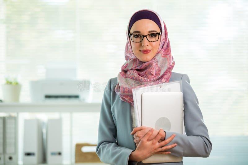 H?rlig ung funktionsduglig kvinna i hijab och glas?gon som i regeringsst?llning ler royaltyfria bilder