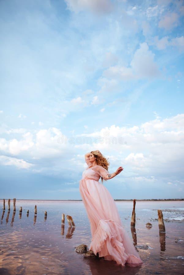 H?rlig ung gravid kvinna som tycker om solen p? den rosa sj?n royaltyfri fotografi