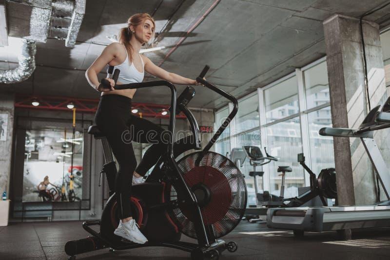 H?rlig ung konditionkvinna som utarbetar p? idrottshallen royaltyfri fotografi
