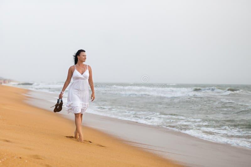 H?rlig ung kvinna i den vita kl?nningen som g?r p? den sandiga stranden som rymmer sandaler Lopp- och sommarbegrepp royaltyfri bild
