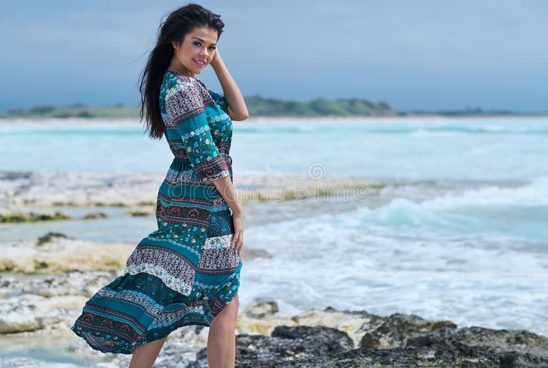 H?rlig ung kvinna i elegant kl?nning p? stranden royaltyfri bild