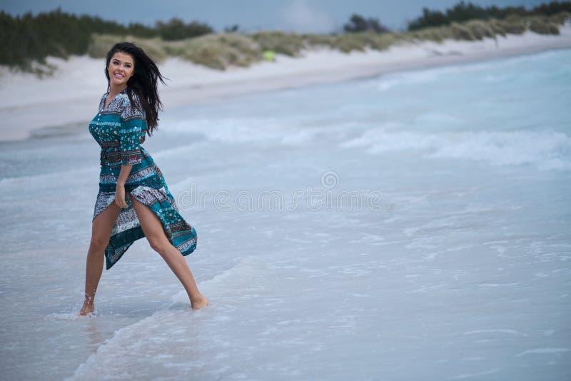 H?rlig ung kvinna i elegant kl?nning p? stranden arkivfoto