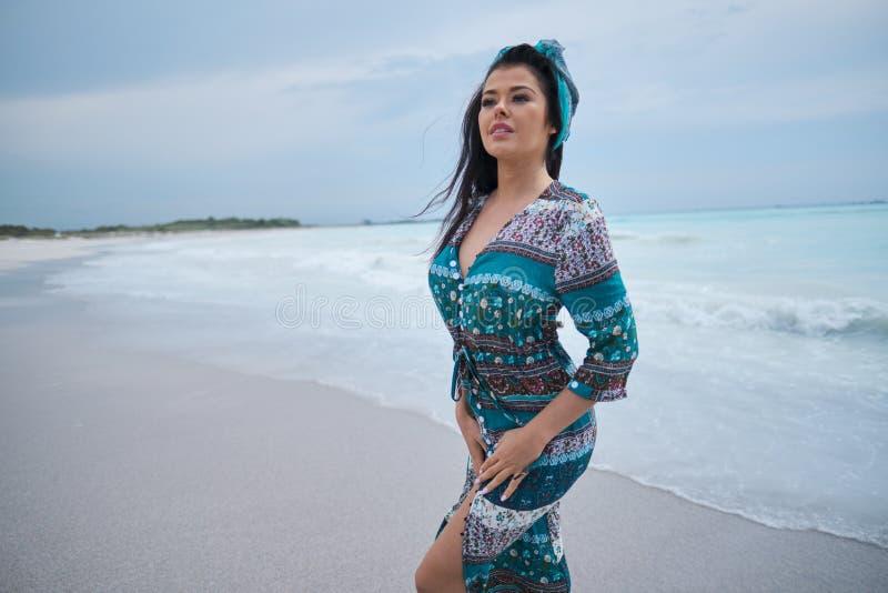 H?rlig ung kvinna i elegant kl?nning p? stranden royaltyfria foton