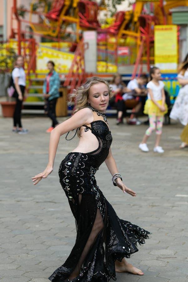 H?rlig ung kvinna i kl?der f?r en tillf?llig stil som isoleras ?ver vit bakgrund Ung flicka som offentligt dansar, arabisk dans,  fotografering för bildbyråer