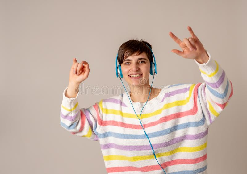 H?rlig ung kvinna i h?rlurar som lyssnar till musik och att dansa som isoleras p? gr? bakgrund royaltyfri foto