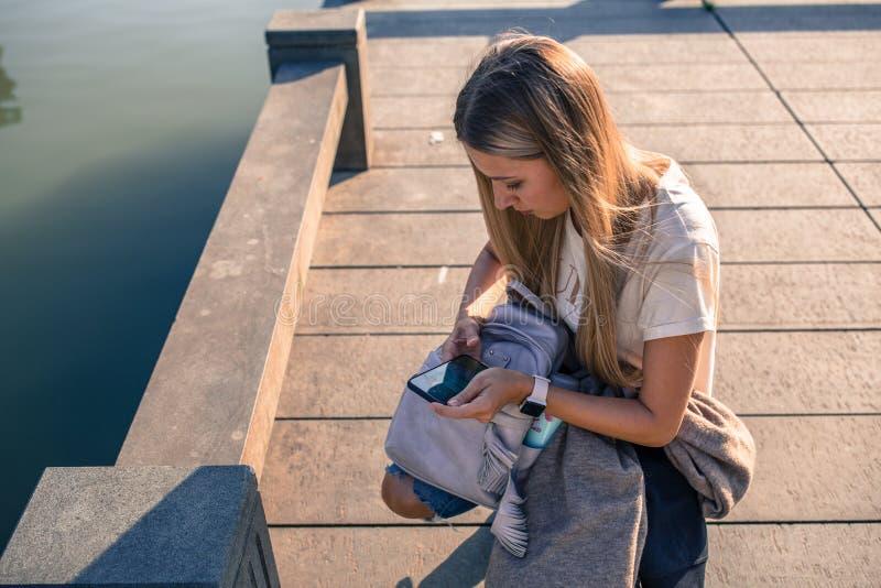 H?rlig ung kvinna med blont h?r genom att anv?nda den utomhus- mobiltelefonen Stilfull flicka som g?r selfie royaltyfri foto