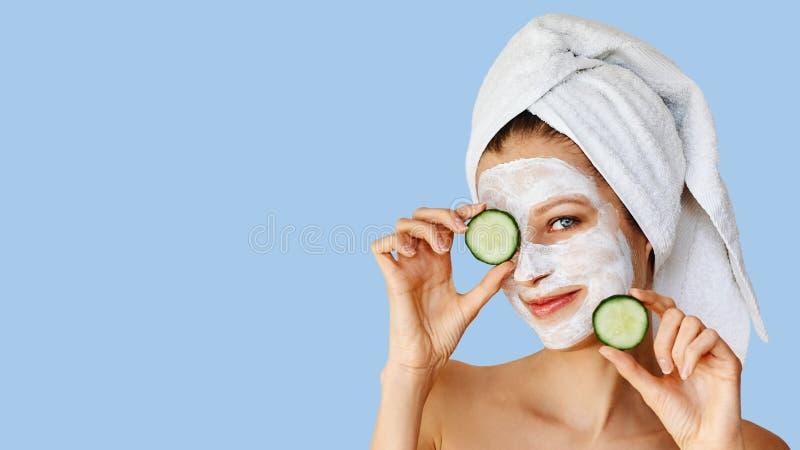 H?rlig ung kvinna med den ansikts- maskeringen p? hennes framsida som rymmer skivor av gurkan Hudomsorg och behandling, brunnsort fotografering för bildbyråer