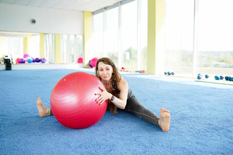 H?rlig ung kvinna med konditionbollutbildning i idrottshall sund livsstil f?r begrepp royaltyfri bild