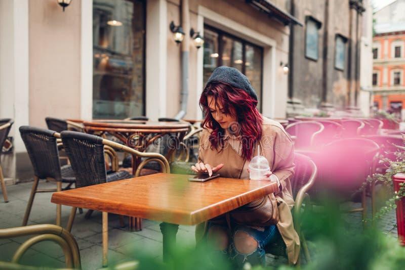 H?rlig ung kvinna som har kaffe i utomhus- kaf?, medan genom att anv?nda smartphonen stilfull flickast?ende royaltyfri bild