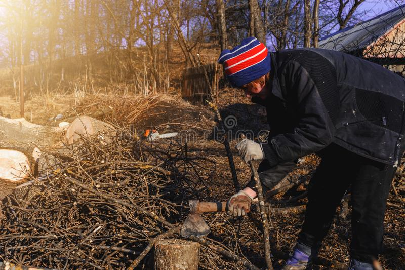 H?rlig ung kvinna som hugger av vedtr? med en yxa i byn under vinter f?r att v?rma huset arkivfoto