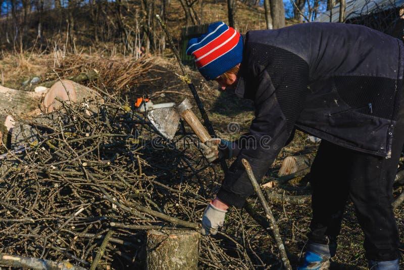 H?rlig ung kvinna som hugger av vedtr? med en yxa i byn under vinter f?r att v?rma huset royaltyfri fotografi