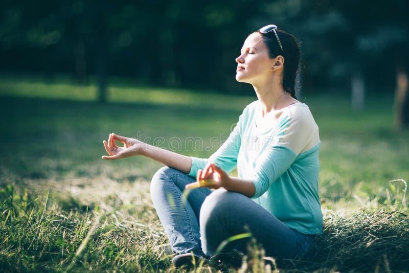 H?rlig ung kvinna som mediterar i den Lotus positionen som sitter p? gr?smattan fotografering för bildbyråer