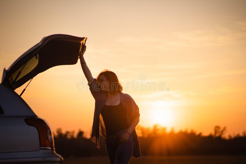 H?rlig ung kvinna som ?r lycklig och dansar i bils stam under en v?gtur i Europa i de sista minuterna av den guld- timmen royaltyfria bilder