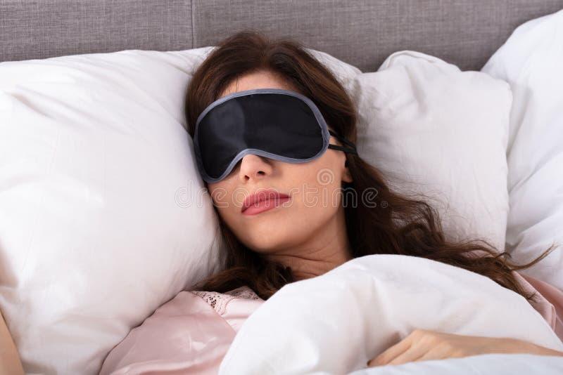 H?rlig ung kvinna som sover p? s?ng arkivfoton