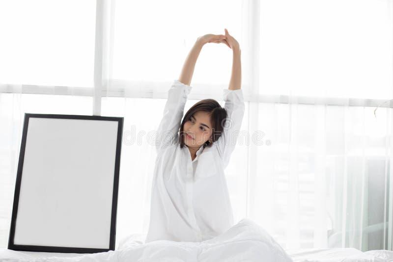 H?rlig ung le kvinna f?r asiatisk kvinna som sitter p? s?ng och str?cker i morgonen p? sovrummet, n?r att ha vaknat upp i hennes  royaltyfria foton