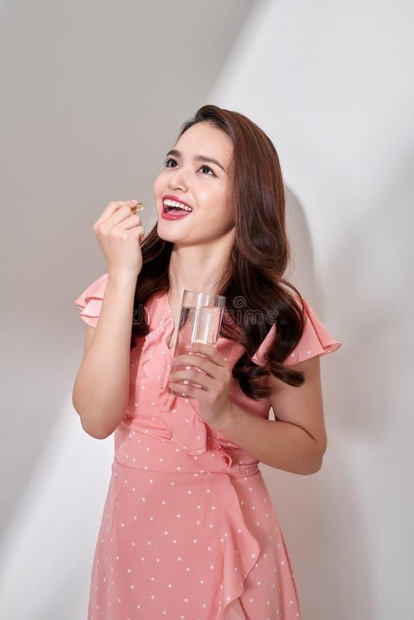 H?rliga asiatiska kvinnor som hemma ?ter vitaminpillret f?r h?lsov?rd arkivfoton