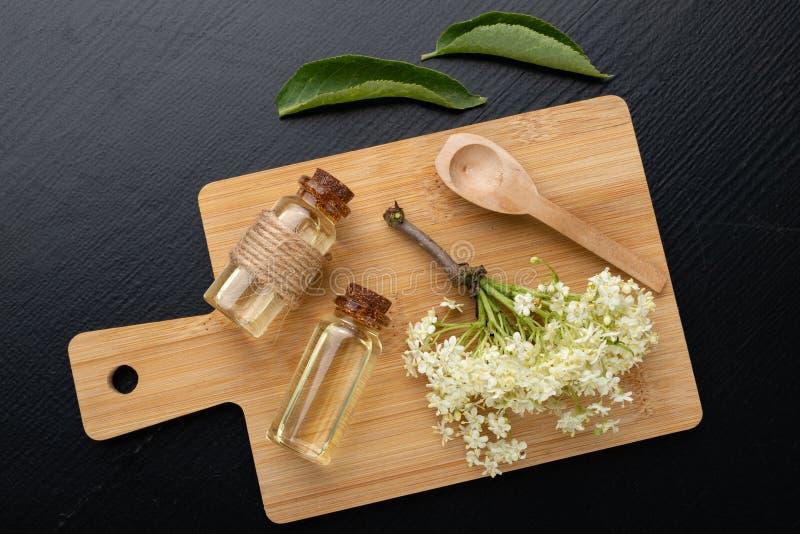 H?rliga blommor av fl?derb?ret och medicinsk fruktsaft i en flaska Naturliga hem- boter f?r f?rkylningar royaltyfria bilder