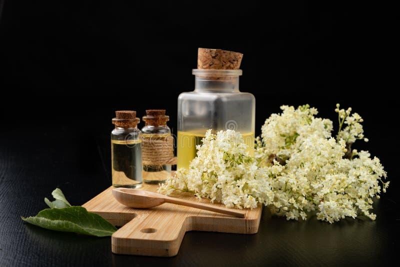 H?rliga blommor av fl?derb?ret och medicinsk fruktsaft i en flaska Naturliga hem- boter f?r f?rkylningar royaltyfri fotografi