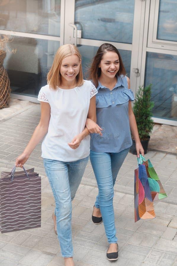 H?rliga flickor med shoppingp?sar g?r vid staden royaltyfri foto