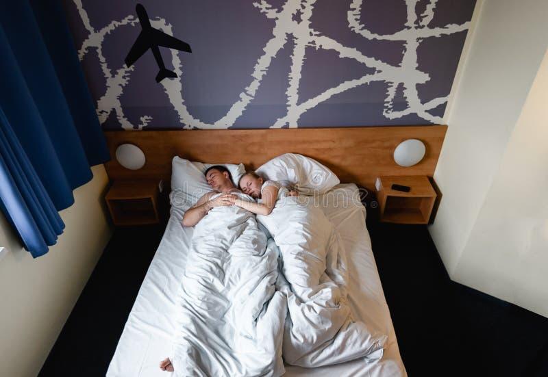 H?rliga lyckliga unga par eller familj som tillsammans vaknar upp i s?ng arkivfoton