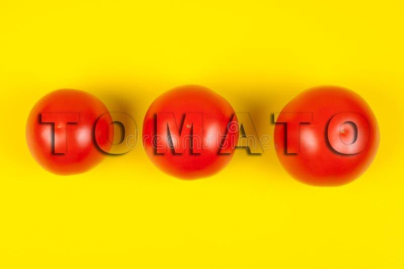 H?rliga nya tomater som isoleras p? gul bakgrund OrdTOMAT fotografering för bildbyråer