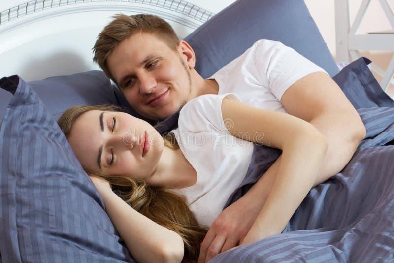 h?rliga underlagpar Grabben vaknar försiktigt hans flickvän i säng i morgonen arkivfoton