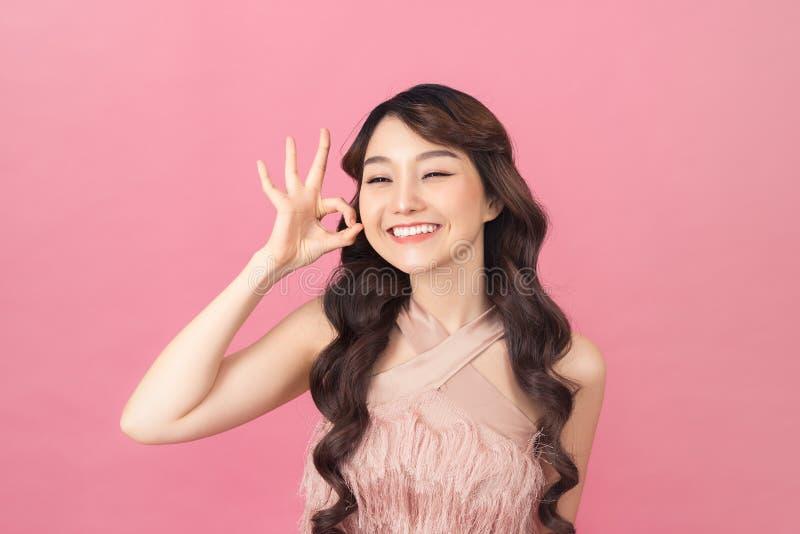 H?rliga unga asiatiska den reko kvinnashowen undertecknar ?ver hennes ?ga p? rosa bakgrund royaltyfri foto