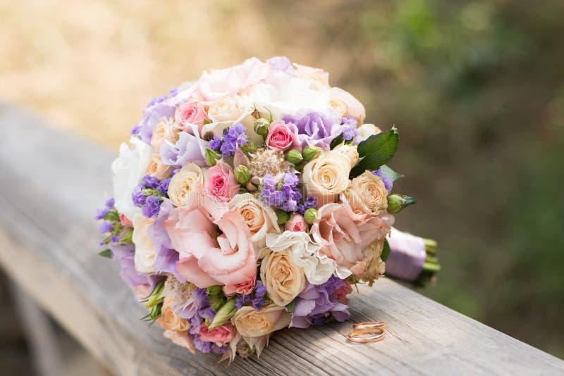 H?rliga vigselringar med buketten av blommor F?rklaring av f?r?lskelse, v?r fotografering för bildbyråer
