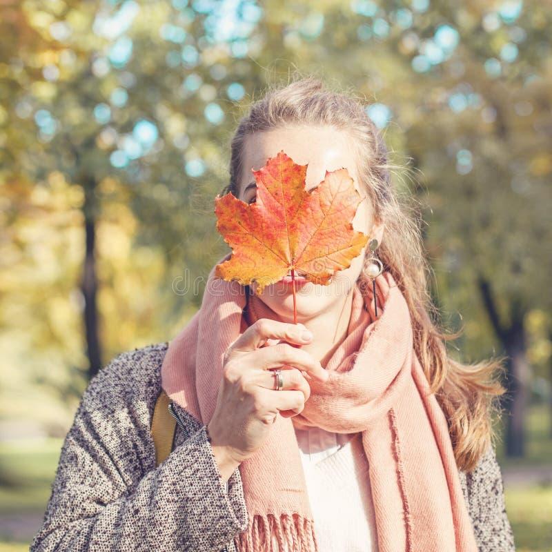 H?rligt Autumn Woman Holding Yellow Maple blad Den romantiska flickan i nedg?ng parkerar arkivfoton