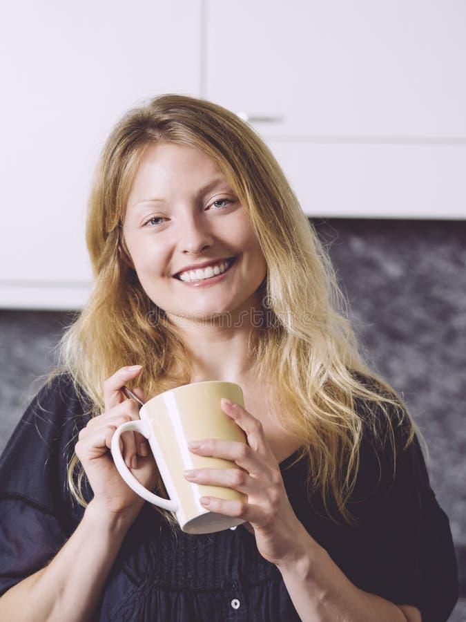 H?rligt blont ha kaffe i hennes k?k royaltyfria bilder