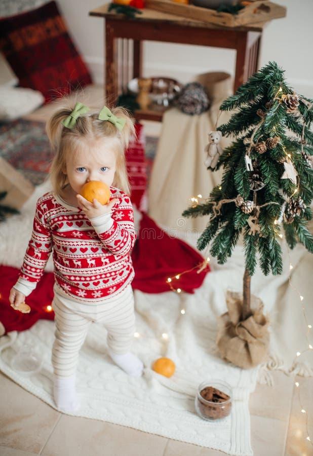 H?rligt lyckligt behandla som ett barn flickan n?ra julgranen royaltyfria bilder