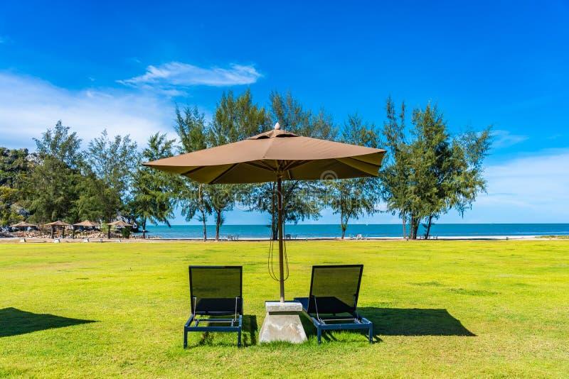 H?rligt utomhus- landskap av havet och stranden med paraplyet och stol omkring d?r fotografering för bildbyråer