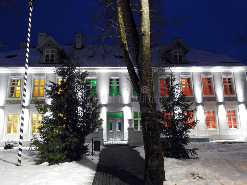Hugo Scheu manor house in Silute town, Lithuania. H. Scheu old manor decorated light which mean Lithuanian flag colors before fiesta - 100 hundred years royalty free stock images