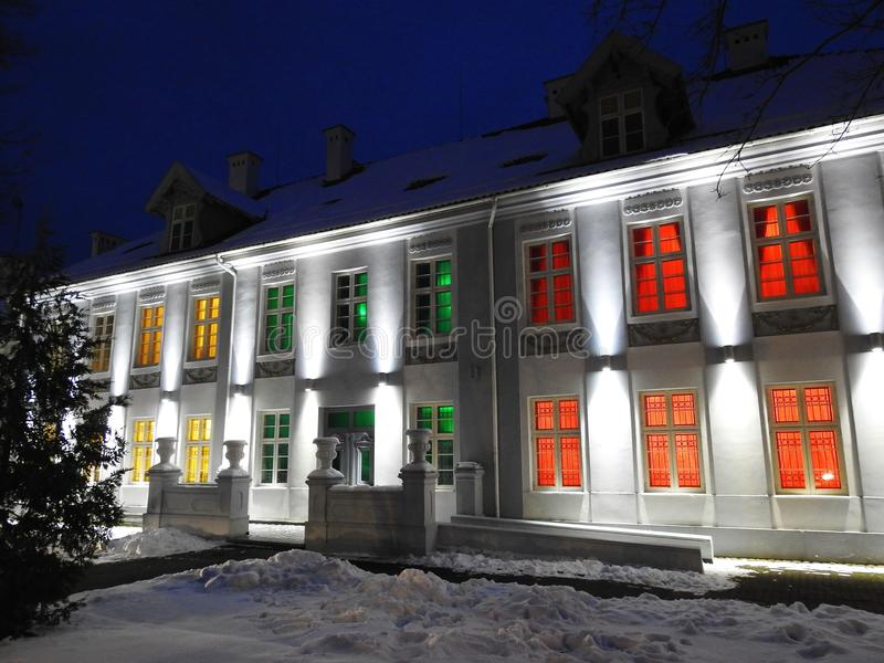 Hugo Scheu manor house in Silute town, Lithuania. H. Scheu old manor decorated light which mean Lithuanian flag colors before fiesta - 100 hundred years stock photography