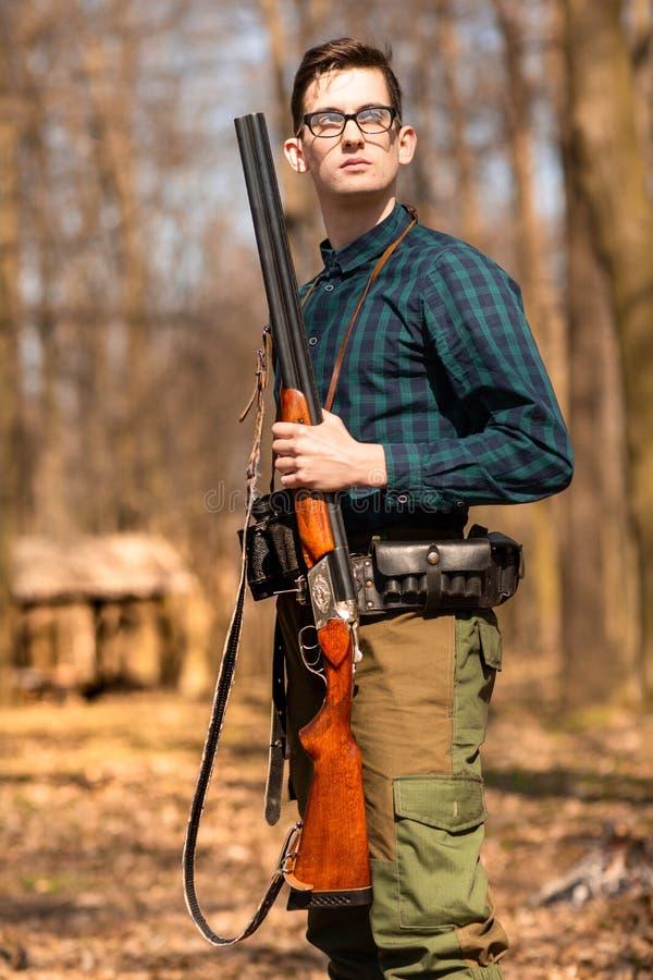 H?stjakts?song Manj?gare med ett vapen Jaga i tr?na royaltyfri foto