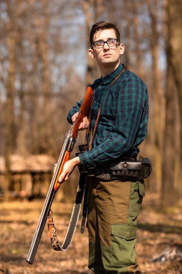 H?stjakts?song Manj?gare med ett vapen Jaga i tr?na royaltyfri fotografi