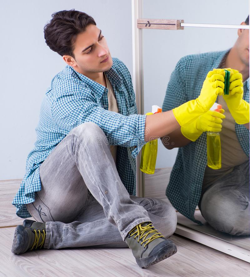 H?tel de miroir de nettoyage de jeune homme ? la maison photo stock