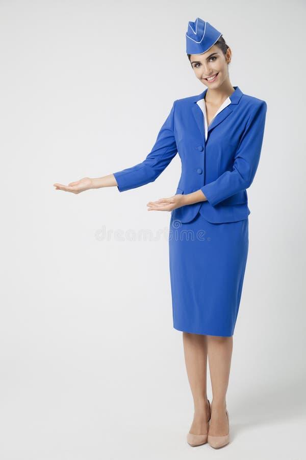 Hôtesse avec du charme habillée dans l'uniforme bleu image libre de droits