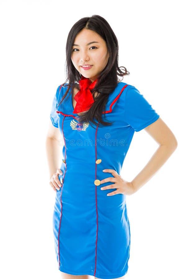Hôtesse d'air asiatique sûre se tenant avec des bras sur les hanches images stock