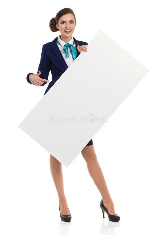 Hôtesse d'air de sourire Holding White Placard et pointage images libres de droits