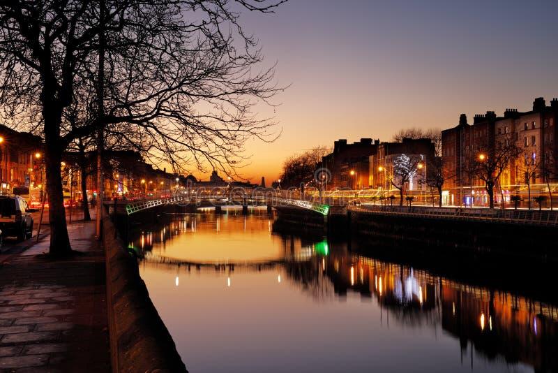 Ha `便士桥梁和河Liffey的北部河岸在都伯林市中心在晚上 免版税库存照片