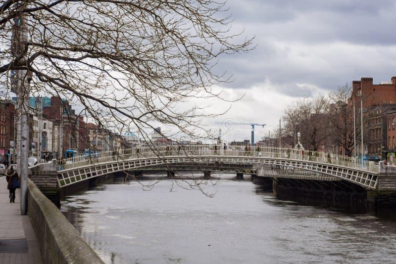 Ha `在利菲河,都伯林,爱尔兰的便士桥梁在与人横渡的冬天 免版税库存照片