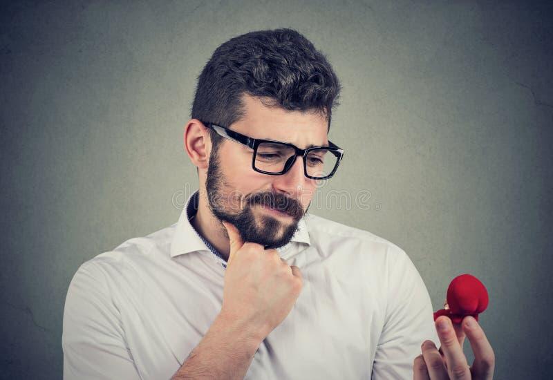 Ha confuso l'uomo che esamina un anello di proposta ed ha dubbi immagine stock