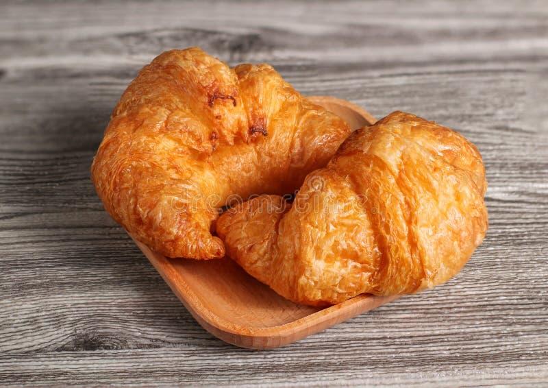 Ha cotto di recente i croissant freschi e saporiti del croissant, isolati sul fondo di legno della tavola fotografie stock libere da diritti