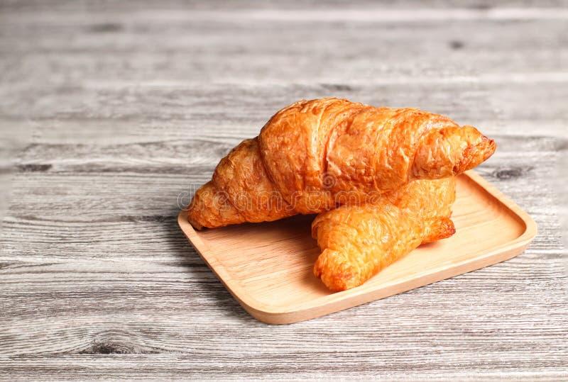 Ha cotto di recente i croissant freschi e saporiti del croissant, isolati sul fondo di legno della tavola fotografia stock