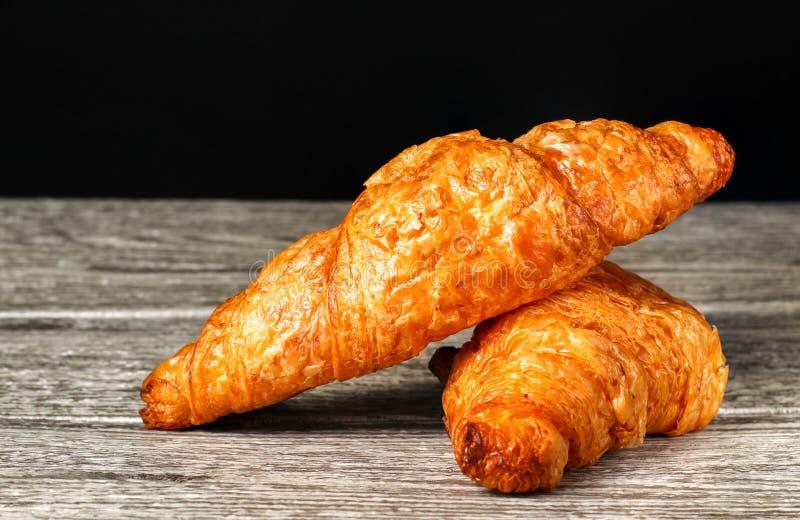 Ha cotto di recente i croissant freschi e saporiti del croissant, isolati sulla tavola di legno immagine stock