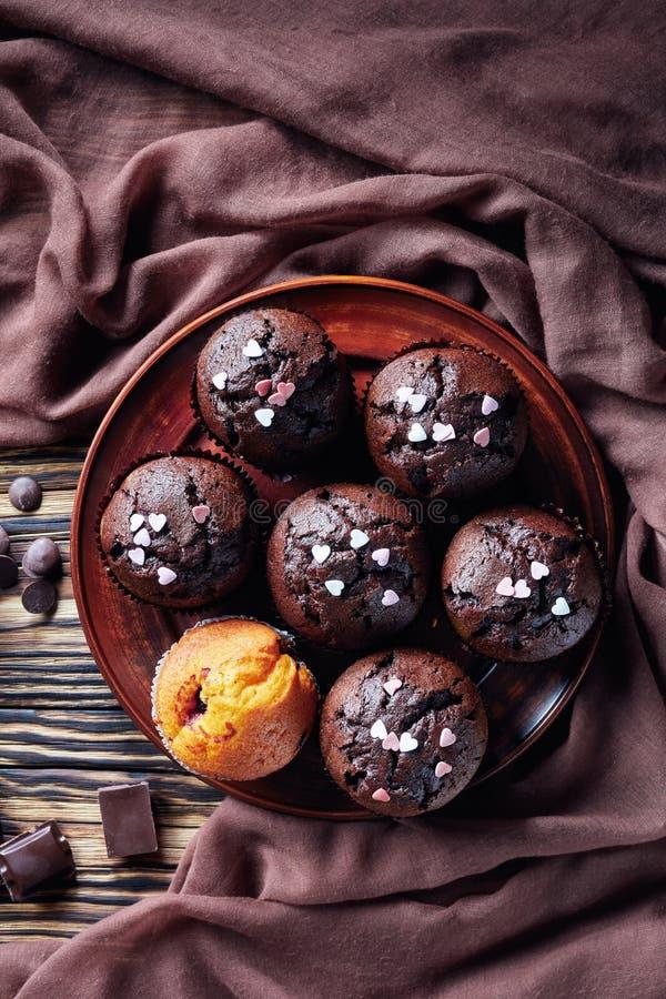 Ha cotto di recente i muffin del cioccolato spruzzati con i cuori della caramella sui piatti delle terraglie fotografia stock