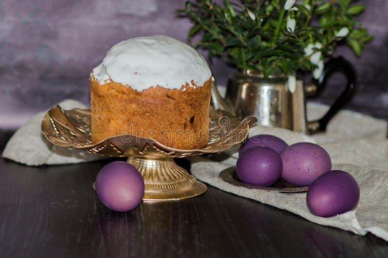 Ha cotto di recente il dolce di Pasqua sul tavolo da cucina coperto di glassa e che decora la guarnizione con le uova porpora Con fotografia stock