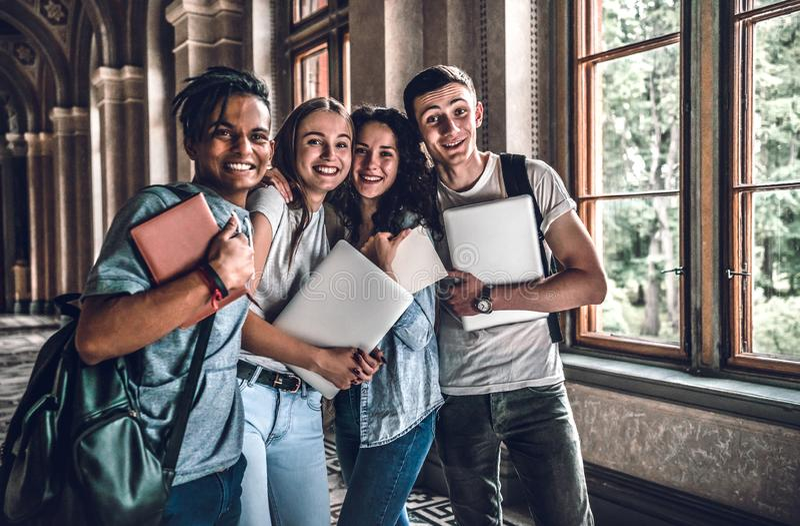 Ha den bästa tiden med vänner Grupp av att le högstadiumstudenter som tillsammans står arkivbild