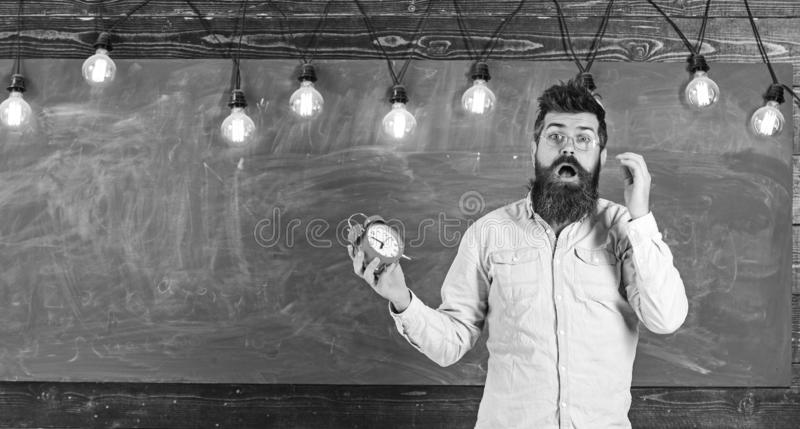 Ha dimenticato circa il concetto di tempo Uomo con la barba e baffi sul fronte colpito in aula L'insegnante in occhiali tiene l'a fotografie stock libere da diritti